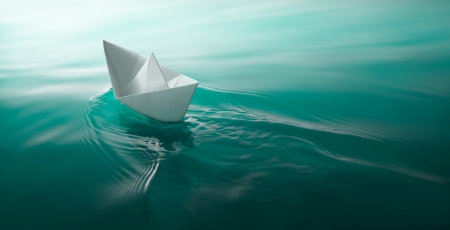 origami paper boat sailing on water causing waves and ripples photo