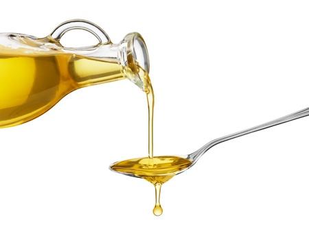 ガラスの瓶からスプーンに油を注ぐ 写真素材