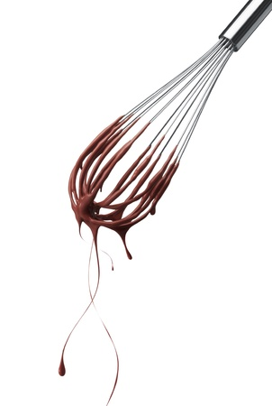 chocolate drop: wire whisk with dripping chocolate isolated on white