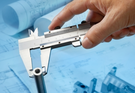 measuring machine part with caliper, blueprint as background