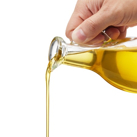 hand holding bottle: pouring olive oil from glass bottle against white background Stock Photo