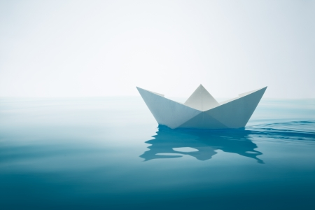 paper boat sailing on water with waves and ripples