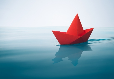red paper boat sailing on water with waves and ripples