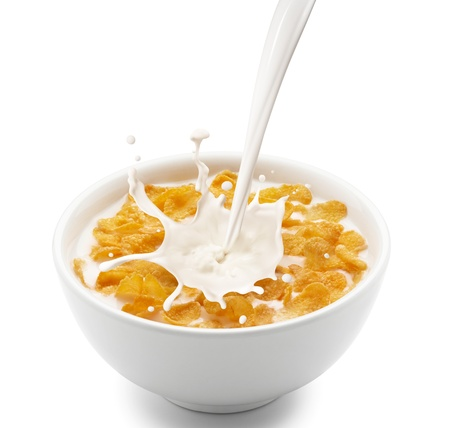 cereal bowl: pouring milk into corn flakes creating splash Stock Photo