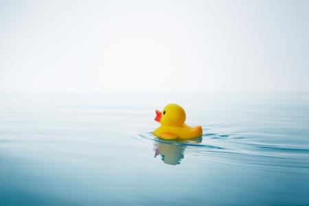 gele rubberen eend zwemmen op het water met golven en ribbels