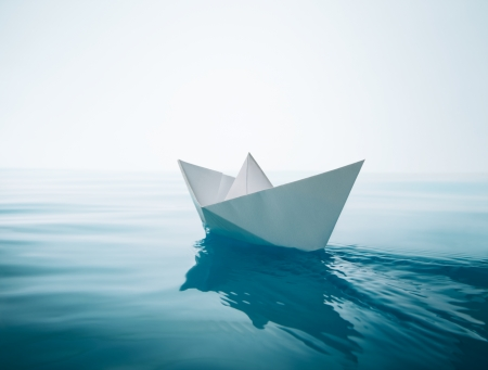paper boat sailing on water causing waves and ripples photo