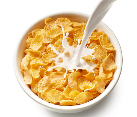 cereal: pouring milk into bowl of corn flakes, top view Stock Photo