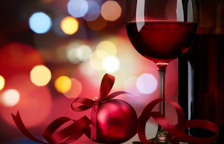 wine background: christmas bauble with red wine against colorful bokeh lights background Stock Photo