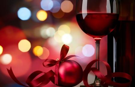 weihnachtsschleife: Weihnachtskugel mit Rotwein gegen bunte Bokeh Lichter Hintergrund
