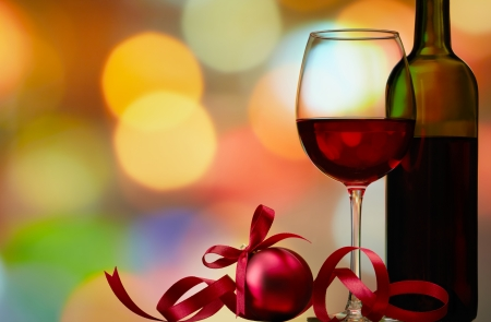red wine: christmas bauble with red wine against colorful bokeh lights background Stock Photo