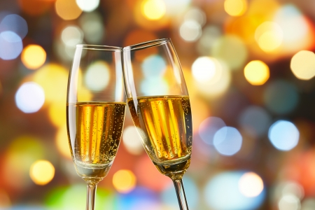 champagne flute: two glasses of champagne toasting against bokeh lights background