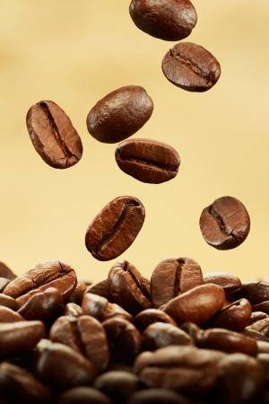 grano de cafe: los granos de caf� cayendo en la pila contra el fondo marr�n Foto de archivo