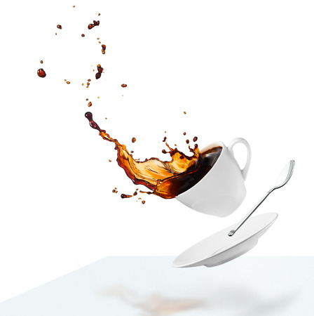 cup of spilling black coffee creating splash