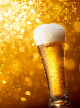 Vaso de cerveza contra el oro luces bokeh de fondo Foto de archivo - 31906241
