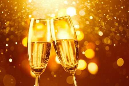 two glasses of champagne toasting against gold bokeh background