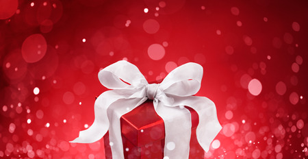 christmas bows: christmas gift against red bokeh lights background Stock Photo