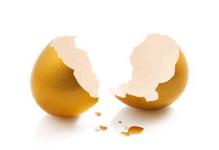 broken golden egg isolated on white background