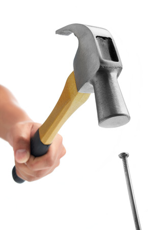 hand holding hammer hitting nail against white background Foto de archivo