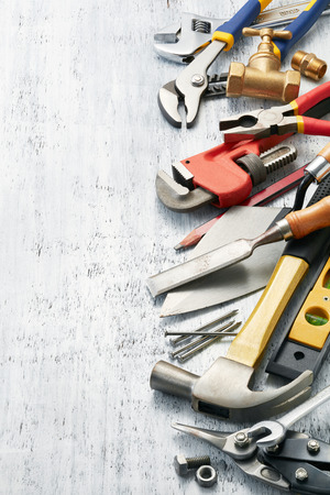 variety of tools on white textured background with copy space