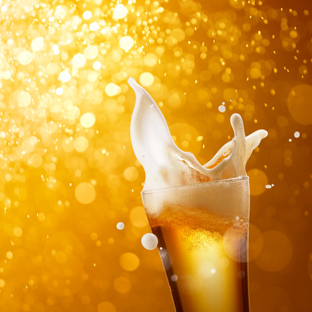 glass of splashing beer against golden bokeh background Stock Photo - 49136298