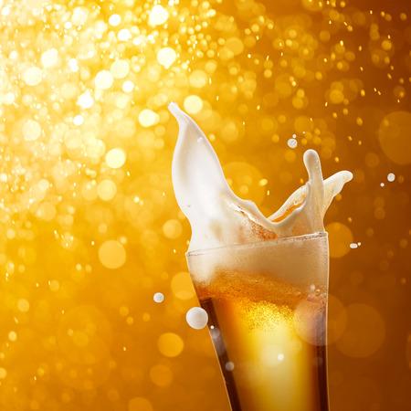 beer bubbles: glass of splashing beer against golden bokeh background