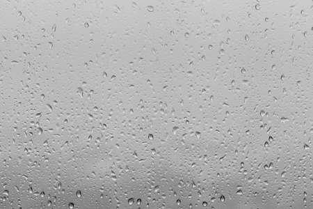 gotas de agua: Foto de gotas de agua en cristales de ventanas superficie con fondo nublado. Diseño natural de las gotas de agua aisladas en el fondo nublado. Foto de archivo