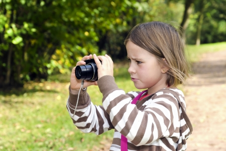 Little girl with the camera in the park photo