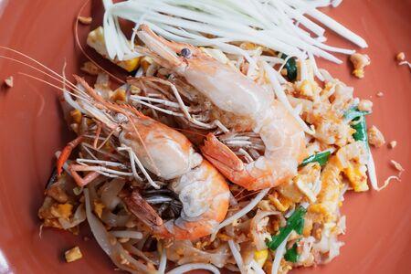 Pad Thai with fresh prawns in an orange plate