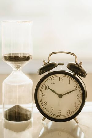 Vintage alarm clock And hourglass In the very bright light from behind Standard-Bild