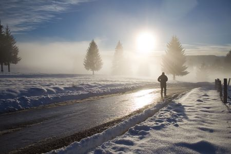 mud and snow: Man walking on road at sunset in winter Stock Photo