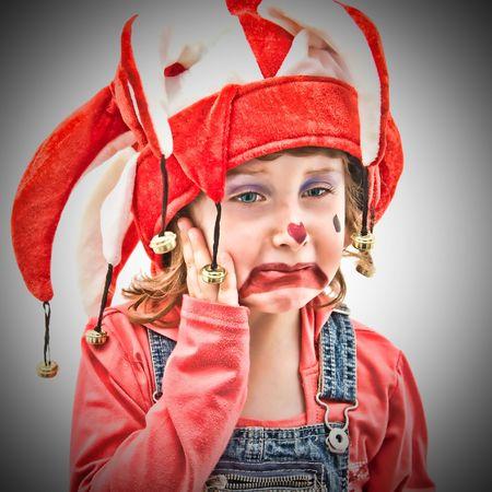 Little girl dressed as a buffon crying. photo