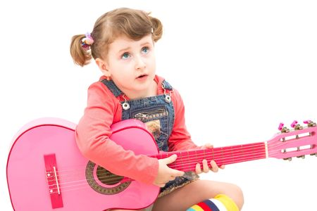 Little girl playing at a pink guitar