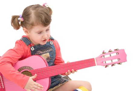 Little girl playing at a pink guitar Stock Photo - 4494231