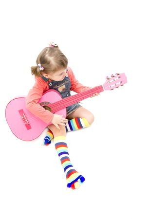 Little girl playing at a pink guitar Stock Photo - 4494190