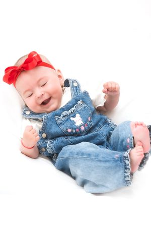Baby girl dressed in jeans laughing outloud photo