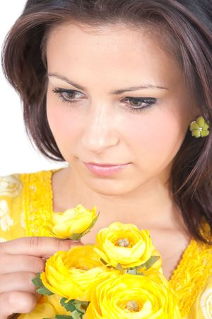 Young woman smelling yellow flowers photo