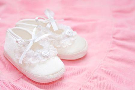 Beautiful baby shoes on pink dress Stock Photo - 5550051