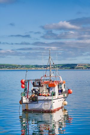 Fishing boat sailing out from the Ballycotton harbour. Stock Photo