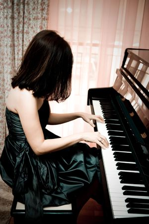 Beautiful young woman playing piano, vintage portrait photo