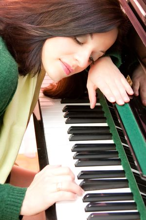 Portrait of a beautiful brunette playing at her piano photo
