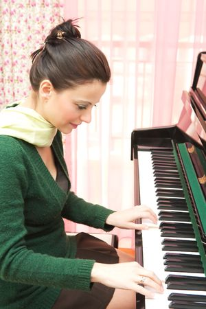 Beautiful young woman playing the piano in her home photo