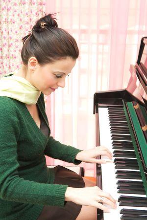 pianista: Hermosa mujer joven tocando el piano en su casa