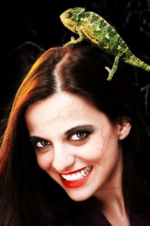 Portrait of a devilish young woman wearing a chameleon in her hair photo