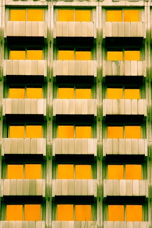 symetry: Symetrycal features of a building with yellow windows.