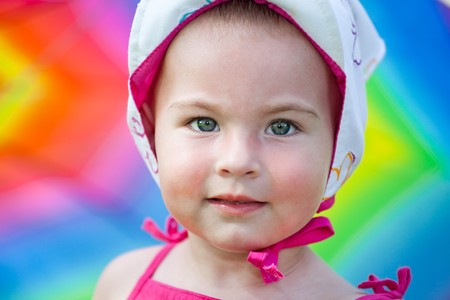 Small baby girl hiding under a big colorful umbrella at a picnic photo