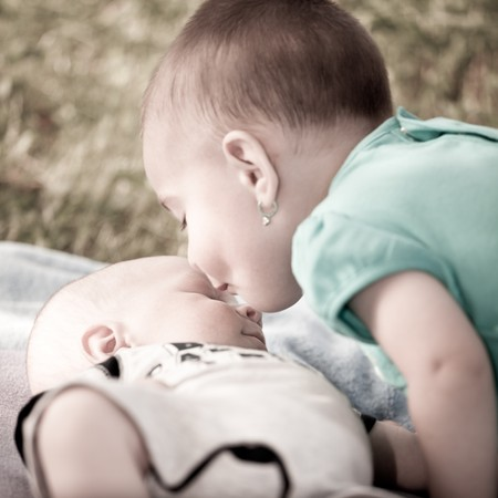 Bay girl giving a kiss to her new born baby brother photo