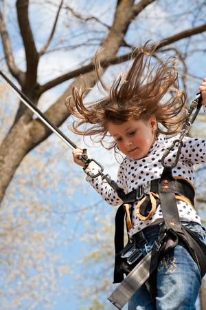Little girl going up and down on a bungee. photo