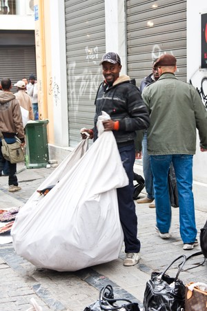 counterfeit: Athens, Greece - February 2010: Immigrants selling counterfeit goods running from the police in downtown