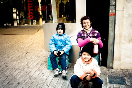 ATHENS, GREECE - February 04: Alexandra and Andrei, aged 4 and 5 with their mother singing for money on Monastiraki street on February 04, 2010 in Athens, Greece.