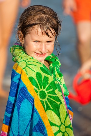 hair wrapped up: Little girl wrapped up in a towel at the beach.